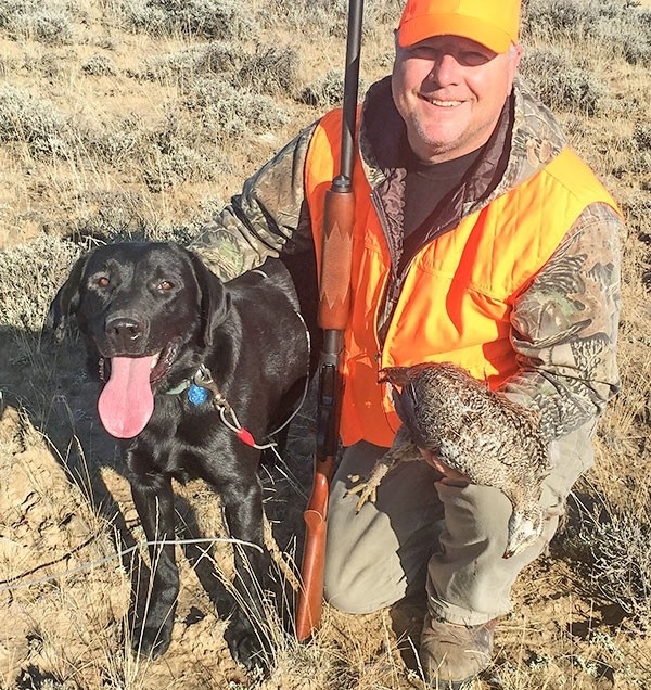 Tribune columnist Mark Davis poses with Gage, a pointing Lab owned by Karl Bear, and his first ever sage grouse during the season last month.