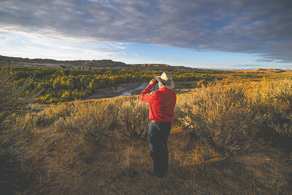 Scott Werbelow, game warden supervisor for the Cody Region, glasses the Greybull River near Meeteetse at sunrise on Tuesday. Werbelow and the nine game wardens who cover the Big Horn Basin are heading into their busy season, as the Wyoming deer season opens Sunday.