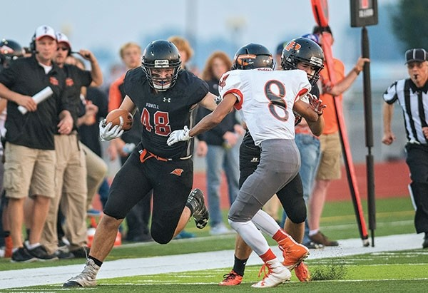Powell's Carson Heinen (48) takes a second quarter reception for a first down with the help of a block on Worland's Andy Deniz (8) by Powell's Garrett Stutzman (17).