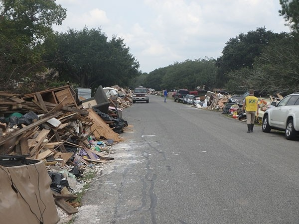 Cody Akin, a missionary in the Houston area for the Church of Jesus Christ of Latter-day Saints, looks over the massive piles of debris that line a street in a town south of Houston. Akin and other missionaries, along with many other volunteers, are helping 'muck out' houses that were flooded by Hurricane Harvey.