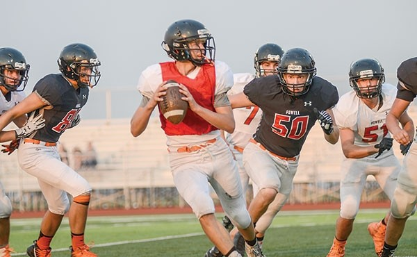 Powell Panther Kaelen Groves, quarterback for the white team, searches for an open receiver as Ryan Good (No. 50) bears down during an intrasquad scrimmage Thursday. The Panthers open the 2017 football season Friday at home against Douglas.