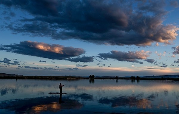 A fisherman throws a lure from a small rocky island at Deaver Reservoir, near Deaver, at around sunset. The facility, built in 1918, is a good fishing spot, especially in winter and early Spring.