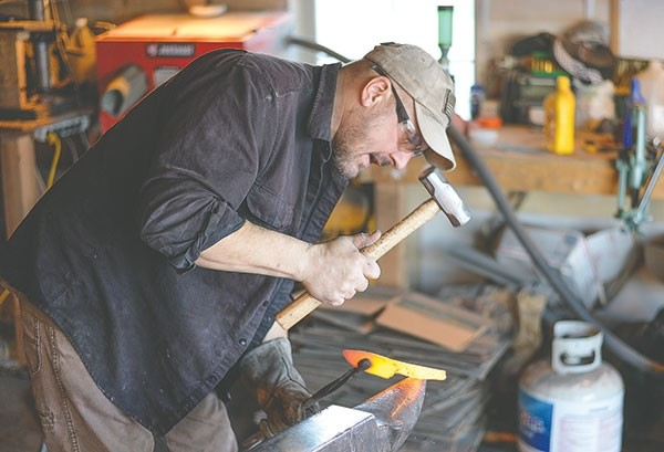 Bladesmith Erich Ouellette shapes a hunting knife with a sledge and an anvil at his shop outside of Powell.
