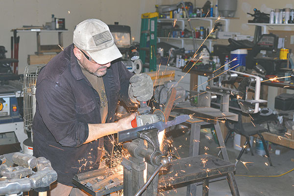 Bladesmith Erich Ouellette cuts a length of 5160-grade steel, a piece of which will be used to build a hunting knife.