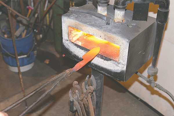 The blade is taken in and out of the forge repeatedly to make the steel easier to shape, as well as to harden the blade.