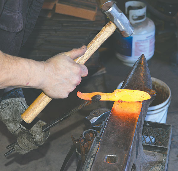 Ouellette uses a sledge to form the shape of the hunting knife. The blade is forged to a point so that the flat side is the blade edge and the curved side will be the spine.