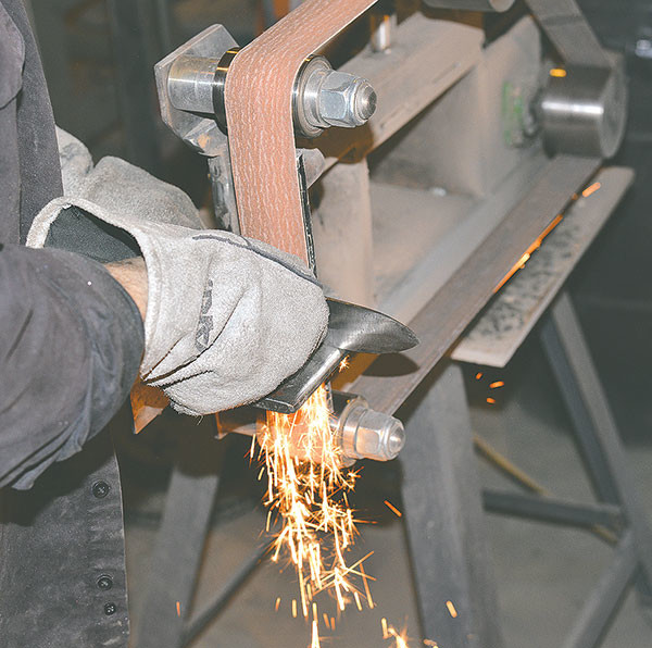 Ouellette uses an industrial belt sander/grinder to give the blade its edge.