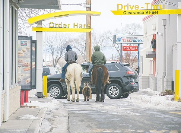 Trajen Collins (left) and Joel Perez drew attention in town and on social media when they rode their horses through the Powell McDonald's drive-thru with a pet goat in tow last week. This photo had been shared more than 3,570 times on Facebook on Wednesday, reaching nearly 430,000 people.