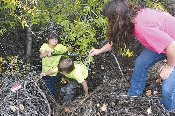 Quincy Barhaug passes up a piece of trash up to his mother, Jamie Barhaug, while Devon Barhaug reaches for a beer can in precipitous and precarious footing. Unsightly litter was plentiful where the family was working Sept. 23. 'I would like to think people would want to change,' Jamie said.