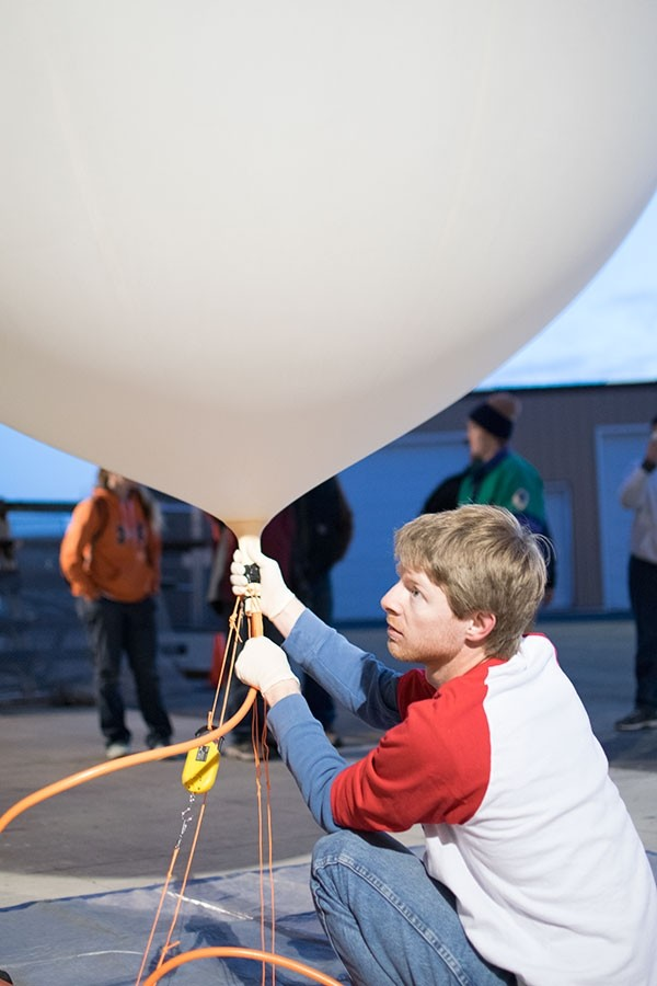 Phil Bergmaier fills a weather balloon with helium on the morning of April 10 at Powell High School. Bergmaier, a graduate fellow in atmospheric science with the University of Wyoming Science Posse, led the weather balloon project for Powell students.