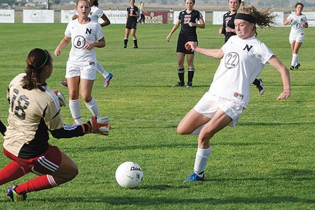 Freshman Hartley Stewart looks to beat a sliding Western Wyoming goalkeeper to this loose ball during home soccer action at Trapper Field last Wednesday. The Trapper women were 4-0 winners in their regular season home finale.