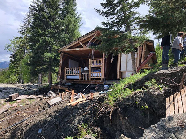 By Wednesday afternoon, Charlie Cooley said his cabin had slid 100-150 feet down the hill off Road XUX. Photo courtesy Charlie Cooley