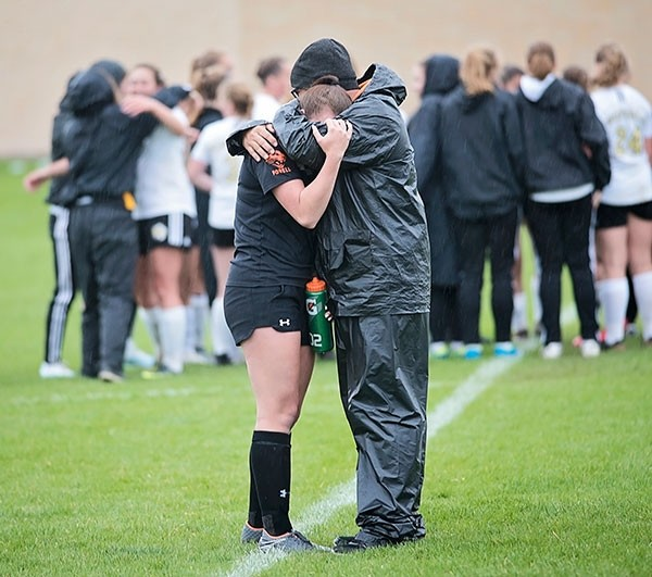 Powell High School head girls' soccer coach Jack Haire hugs his daughter Joey after the Lady Panthers' 3-2 loss to Buffalo in the 3A state play-in game Friday in Worland. The loss brought an end to Powell's season.