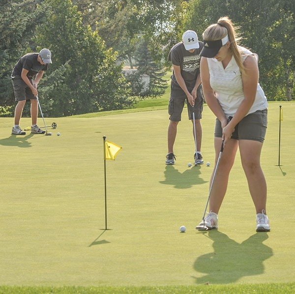 Panther golfers Mycah Wainscott (right) and Crandell Sanders (far left) practice putting before a tournament last season. Wainscott shot a 91 to finish fifth at last week's Powell Invite, while Sanders finished in seventh on the boys' side, carding an 81.