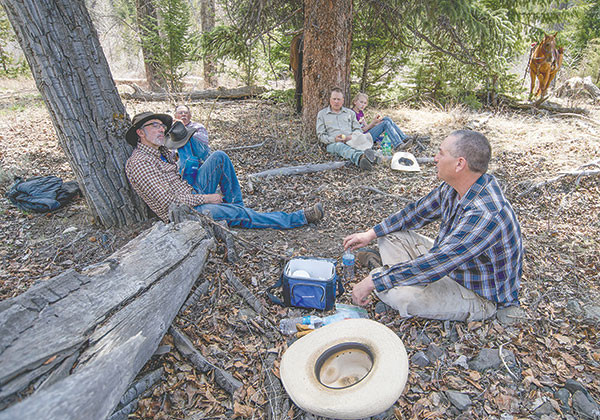 Frank Fagan (front, clockwise) Blair and Jason Brengle, Dale Olson and Bud Melcher stop for lunch in the shade near Ishawooa Creek while volunteering to remove a fence.