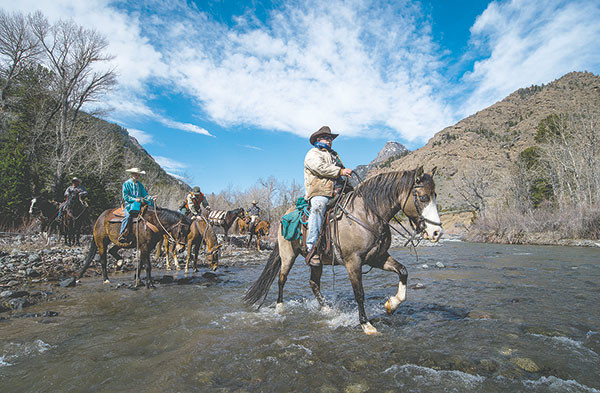Noble Handley, member of the Shoshone Back Country Horsemen, crosses Ishawooa Creek en route to removing an isolated fence standing in the way of wildlife migrations in the Shoshone National Forest.