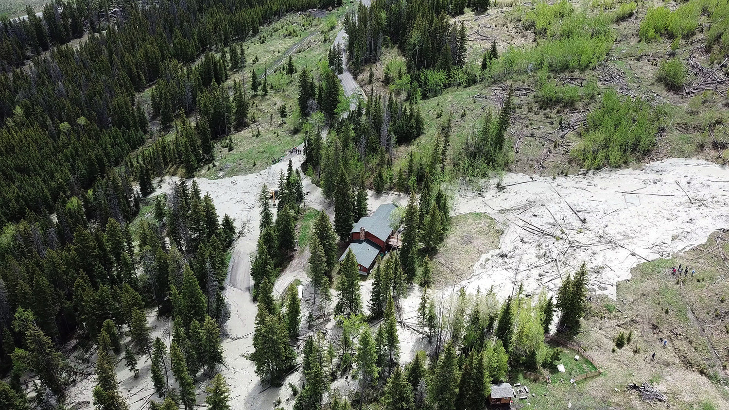 In this shot captured by a drone, Charlie and Jamie Cooley's cabin is seen surrounded by mud and other debris as it slides down Hunter Peak and across Road XUX (the Squaw Creek Road) in the Crandall area earlier this week. The Cooleys' cabin — along with one owned by Ardell Smith that's just outside the bottom of this frame — suffered substantial damage.