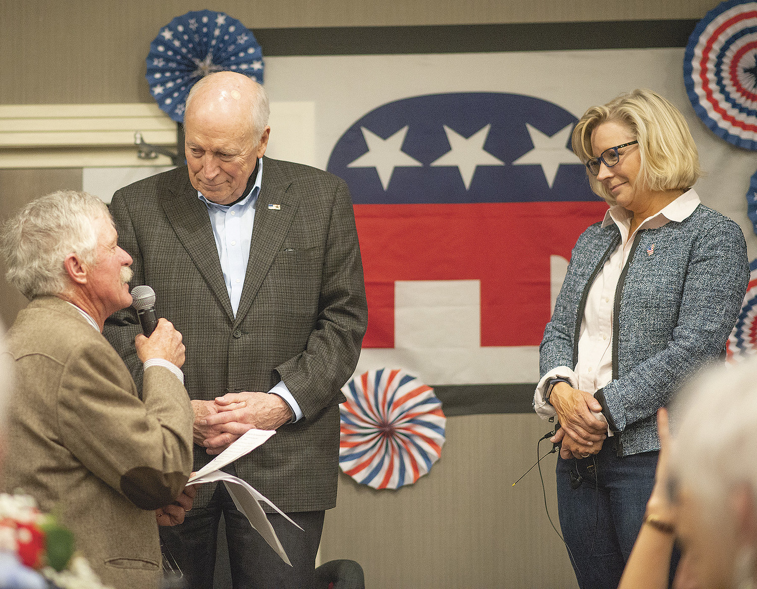 Martin Kimmet, chairman of the Park County Republican Party (left), introduces former Vice President Dick Cheney as U.S. Rep. Liz Cheney, the vice president's daughter, looks on at the party's Lincoln Day Dinner in Cody on Friday night.