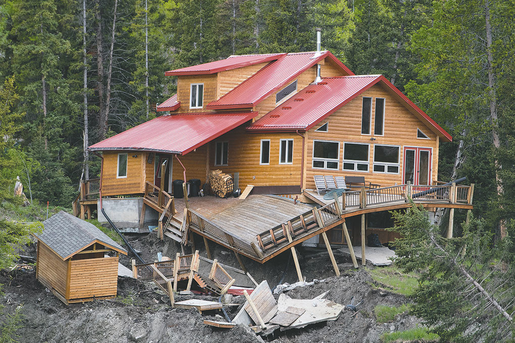 The Smith cabin was pushed from its foundation and is precariously positioned on the slope above Squaw Creek Road on Thursday. The cabin was recently built after a fire destroyed the former cabin on the property.
