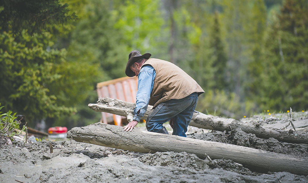 Rick Wogoman walks through thick mud — feet deep in some places — to check on cabins caught in a mudslide in Crandall on Thursday.