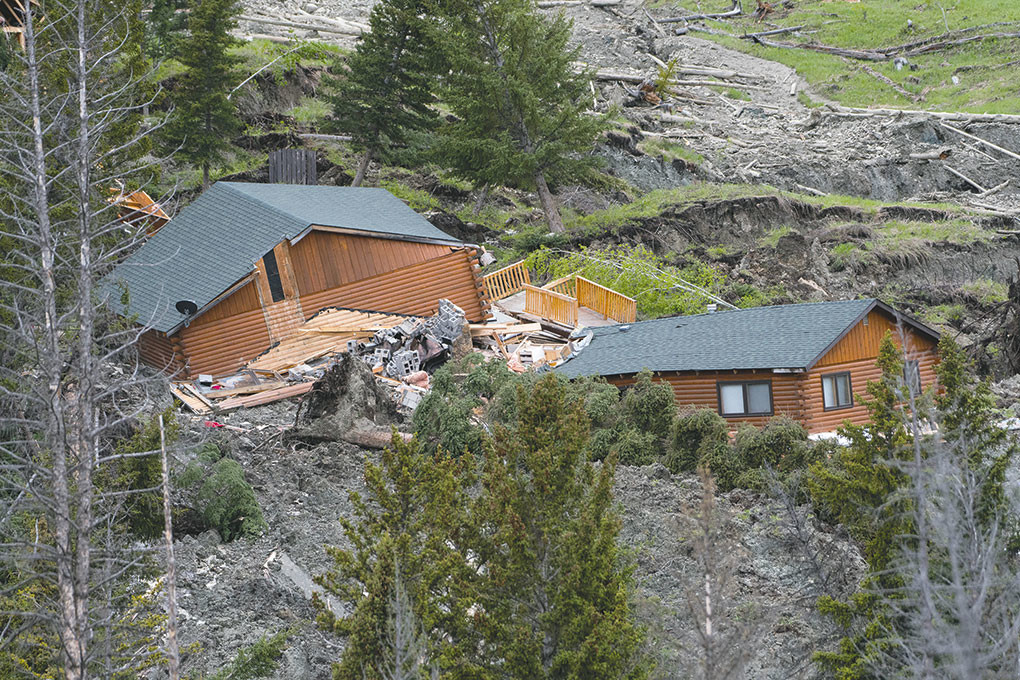 Debris flows down the side of Hunter Peak in Crandall just above the Cooley family cabin on Squaw Creek Road on Thursday. The mudslide totaled two cabins and threatens others in the area.