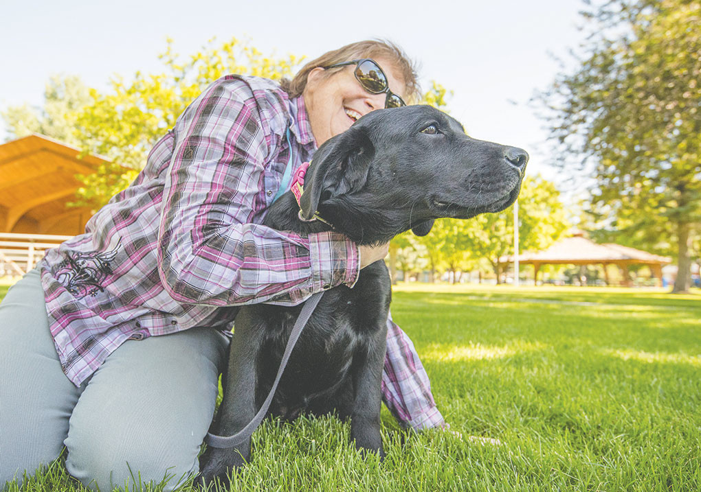 Linda del Toro snuggles with Sabra, an English Lab, after meeting her for the first time. Sabra will be trained as a service dog for combat veterans who suffer from traumatic brain injury or PTSD.