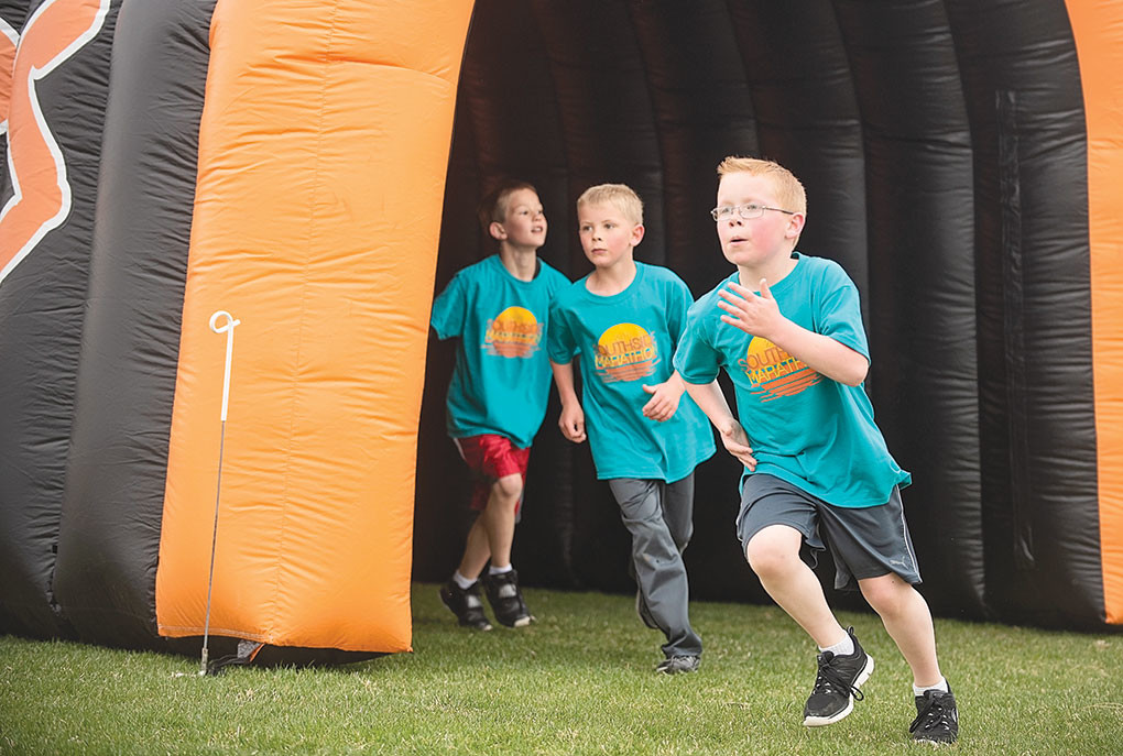 Sam Williams, Landon Petersen and Ira Hovey pass through the inflatable tunnel and make their final lap of the marathon.