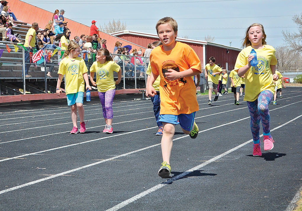 Cannon Tolman from Clark Elementary School (center) and Zofia McMillan from Parkside Elementary School run their final marathon laps last month. Pictured in the background is Isi Tobin (far left) and Tempie Day.