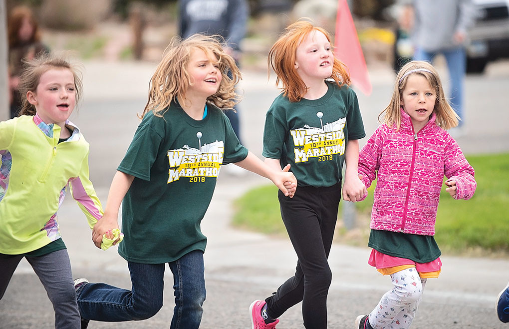 Westsiders Kylee Johnson, Bailee Gallagher, Jacey Stafford and Willow Tajan run hand-in-hand while nearing the finish line.