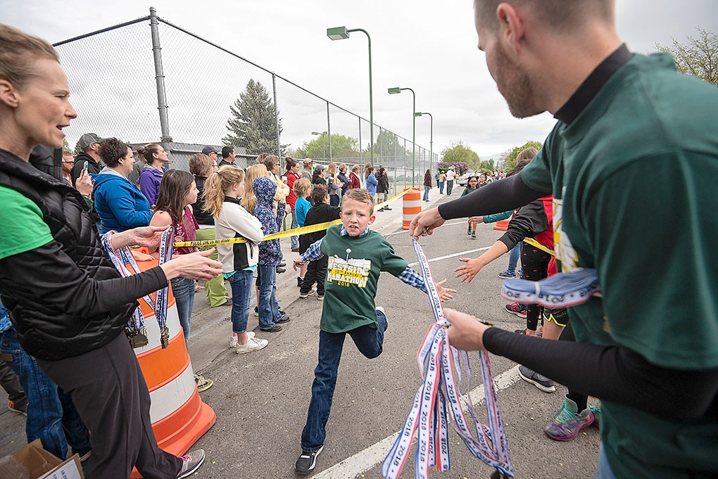 Mason Green finishes his marathon to congratulations from Angela Woyak, Westside's principal, and a medal from PE teacher Luke Robertson.