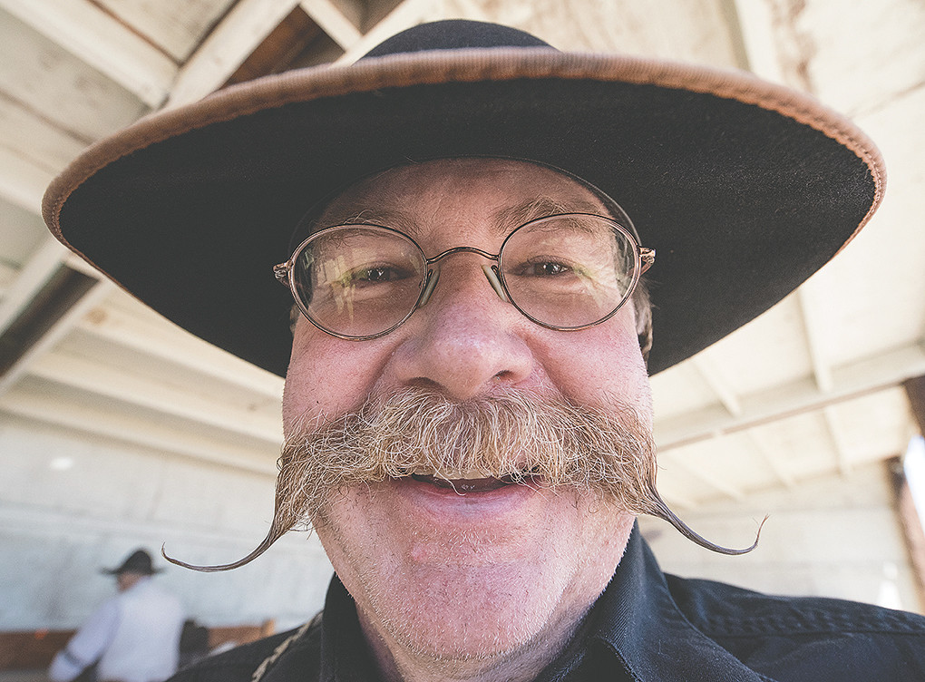 Paul Hoeft, president of the Colter's Hell Justice Committee chapter of the Single Action Shooting Society, sports a handlebar moustache and a broad smile during June cowboy action shooting competition. Members dress in 19th century outfits for the competitions.
