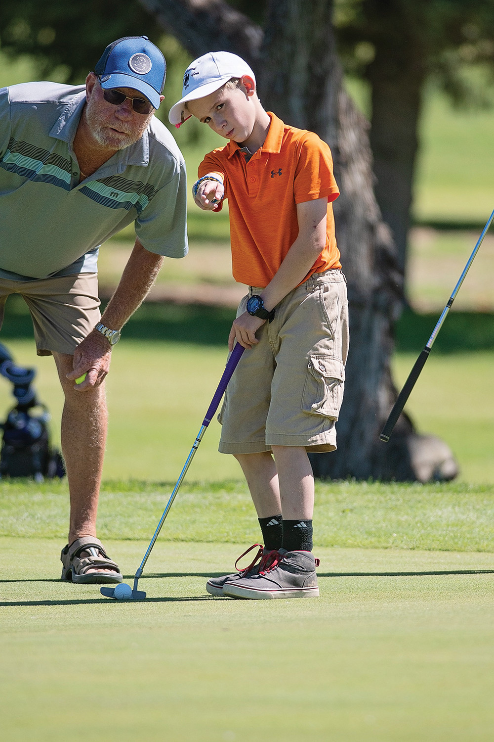PGC member Marc Saylor (left) discusses putting strategy with teammate Jacob Thomas.