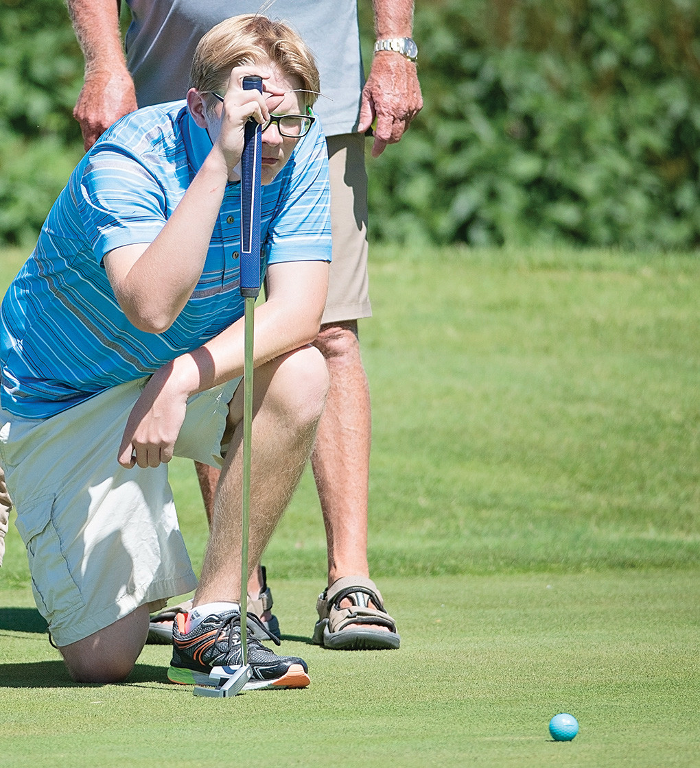 Kirk Thomas, 16, lines up a putt on Hole 16 Wednesday morning during the Members-Juniors Golf Scramble.