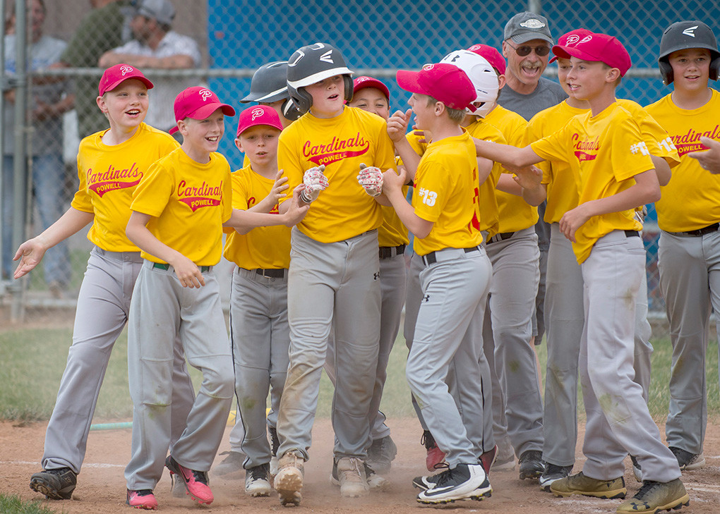 Brock Johnson of the Powell Cardinals is welcomed to the plate by his teammates after hitting a walk-off home run for a 1-0 win in the Little League Majors championship game.