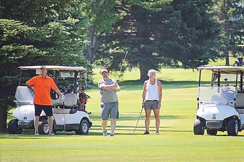 Billy Sommerville (left) and Heather Faxon (right) watch intently while Paul Faxon fires a shot at the pin on hole No. 12 at the Powell Golf Club during Friday's Powell High School Alumni Association's Panther Open. Sommerville and Faxon were both members of the Powell High School Class of 1988.