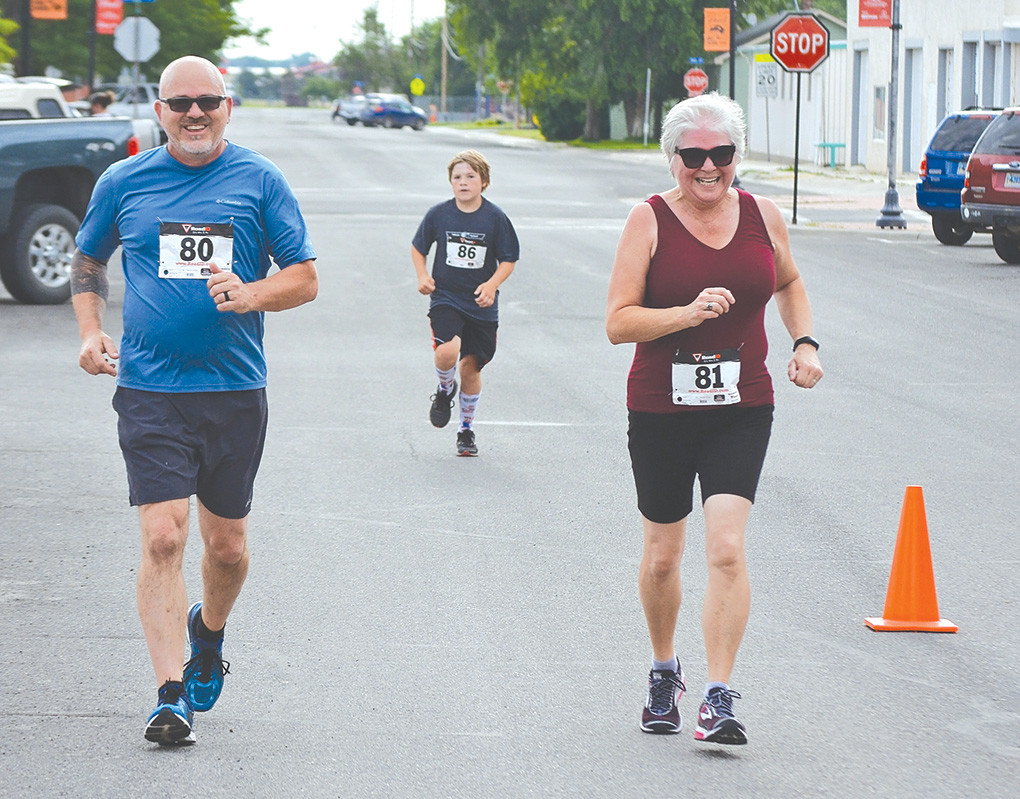 Kurt Kinsey and Linda Brown are all smiles as they make their way to the finish line of the 2018 Rec de Plaza 5K on Saturday at Plaza Diane, with Dane Lauritzen hot on their heels.
