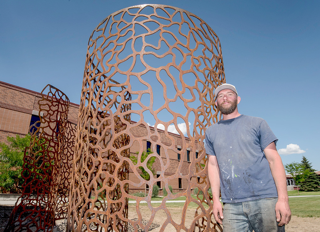 Artist Jodie Roth Cooper poses with his sculpture, 'Infinite Pattern S's' after a long day of installing the new piece on the east side of Northwest College's Yellowstone Building.