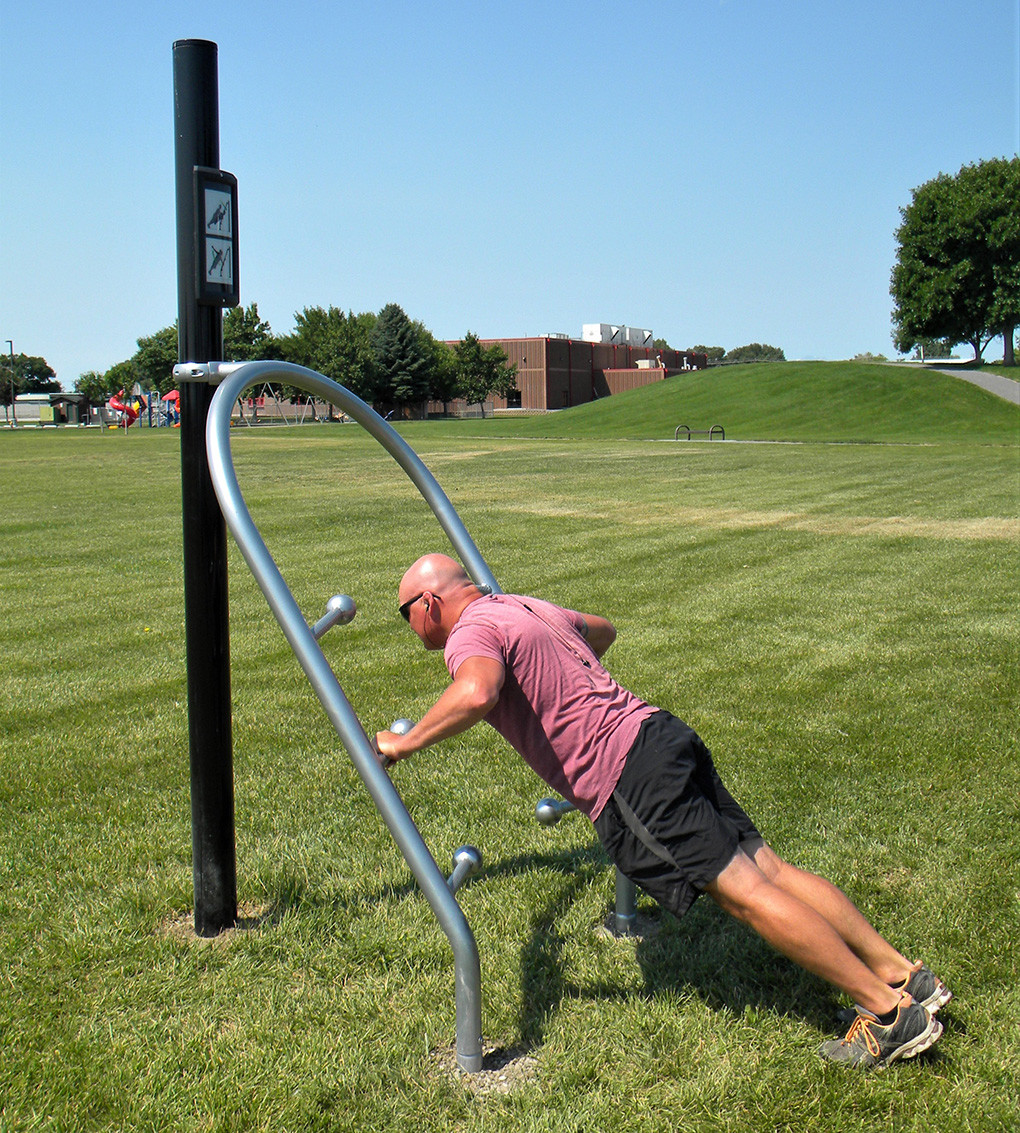 City of Powell employee Tim Jordan demonstrates how to use the stable press fitness station at Homesteader Park.