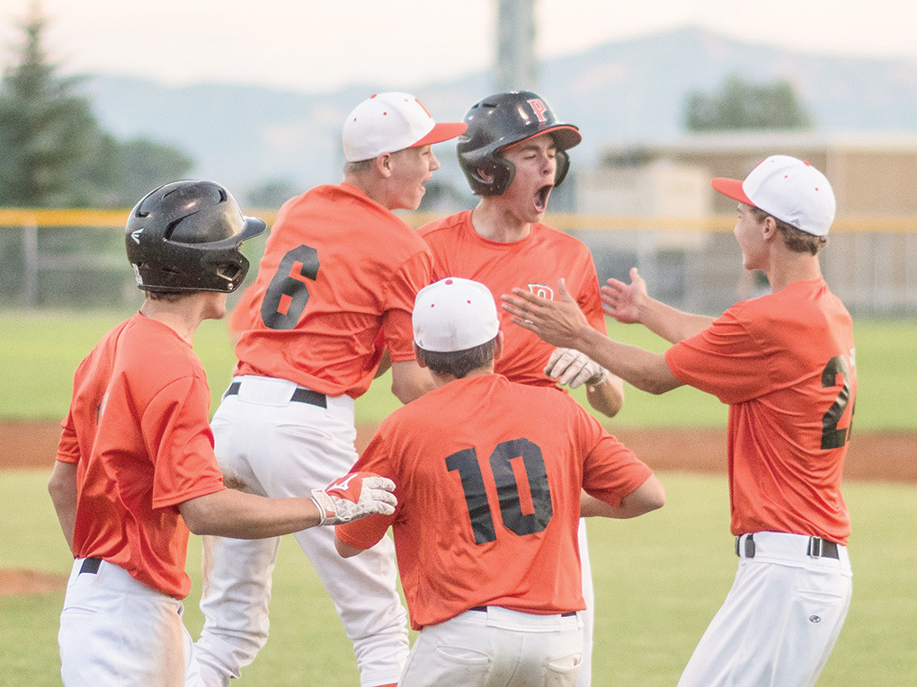Pioneers baserunner Jesse Brown, center, is mobbed by teammates after scoring the gamewinning run against Green River Tuesday at Ed Lynn Memorial Field. The 7-6 win was the home finale for the Pioneers this season.