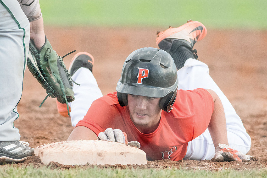 Pioneers baserunner Garrett Stutzman dives safely back to first in a Tuesday game against Green River. Powell won 7-6 in extra innings.