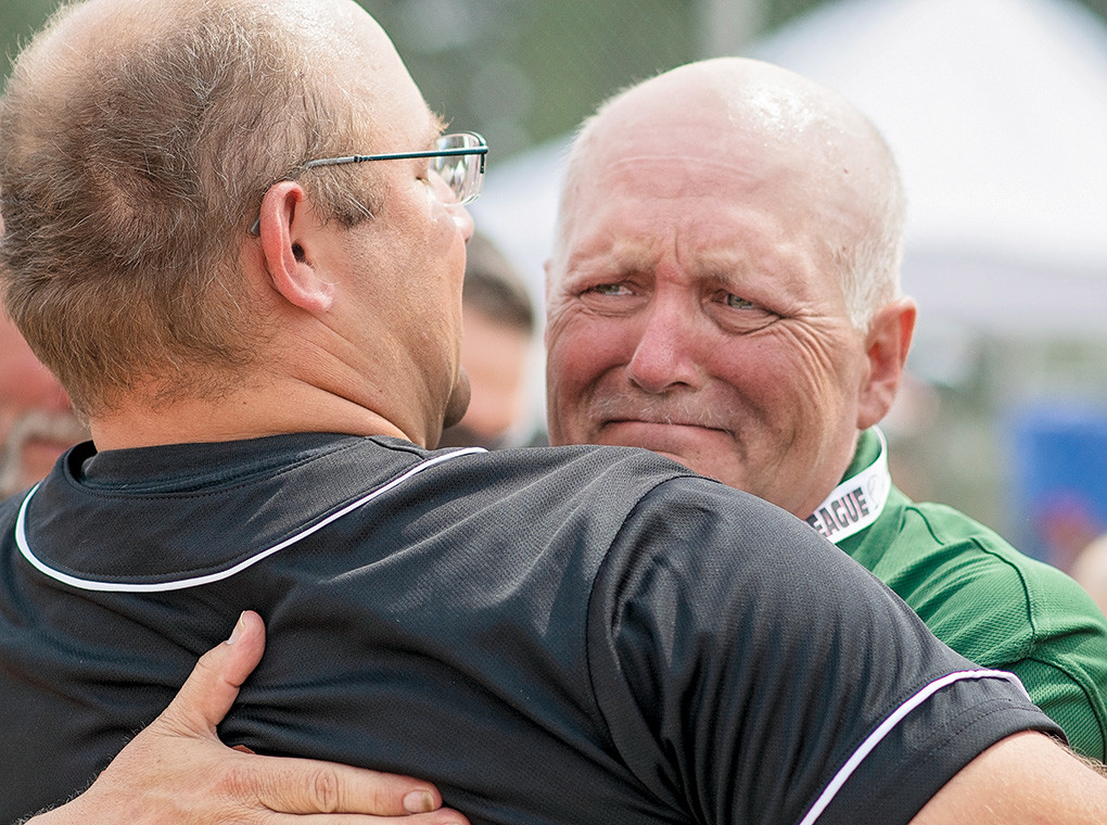 Longtime Little League umpire Calvin Sanders (right) hugs Powell All-Stars coach Brian Orr following Powell's win in the District 1 Championship game against Big Horn on Saturday. The All-Stars wore the number 13 on the back of their caps to honor Sanders, who is battling cancer.