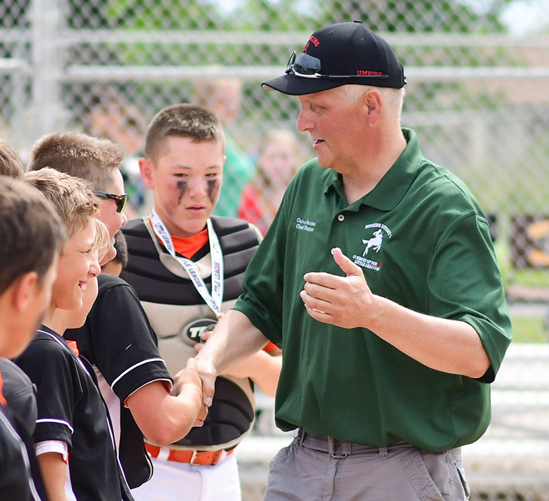 Calvin Sanders shakes hands with the Powell All-Stars during Saturday's medal presentation ceremony at the District 1 Tournament. A longtime umpire and supporter of Powell Little League, Sanders was the inspiration for the Powell team in their 6-2 win over Big Horn.