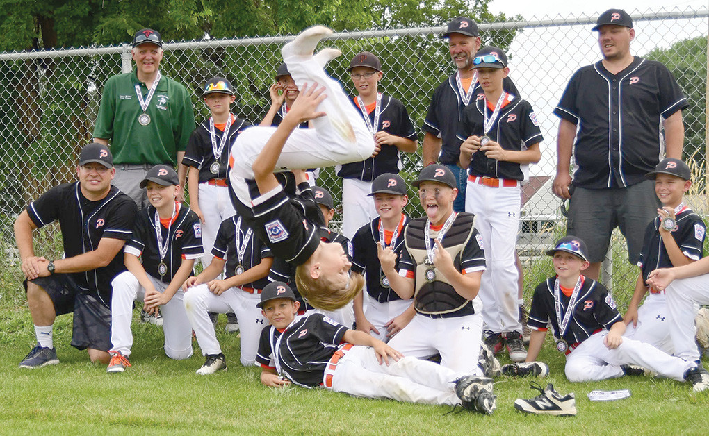 Rayce Degraffenreid flips out in front of his teammates Saturday after the District 1 Championship game. From back left: Calvin Sanders, Dylan Payne, Isaiah Woyak, Cade Queen, Coach Heath Worstell, Jacob Gibson and Coach Mike Gibson. Front Row: Coach Brian Orr, Jacob Orr, Brock Johnson, Jhett Schwahn, Brody Payne and Ethan Welch. Lying in front: Treyson Norris.