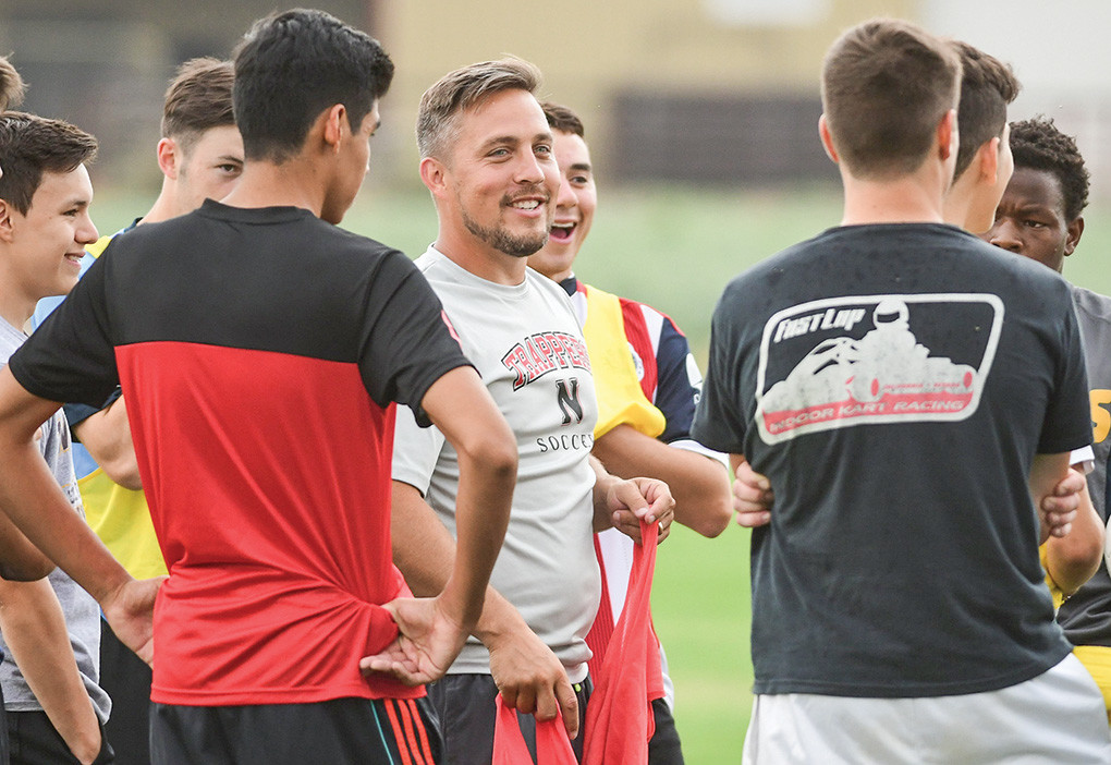 Trappers interim head coach Bobby Peters (center) addresses the team during a Friday practice at Trapper Field. Peters will be doing double duty this season as the head coach for both the men's and women's teams.