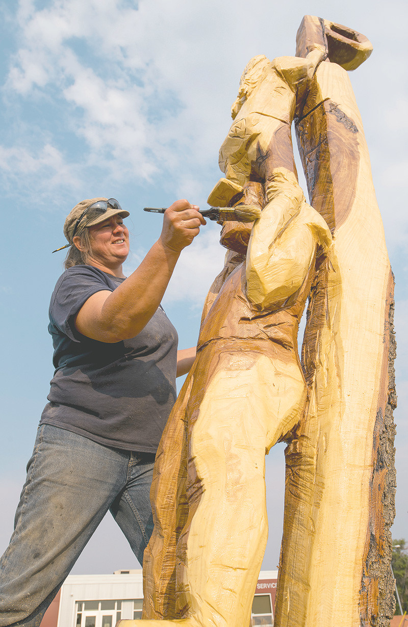 Christy Muecke applies a varnish to the north side of a sculpture, which depicts two students working together to install a Powell 'P' on a pole. The varnish will need to be applied at least once a year to keep sprinklers and the sun from harming the wood