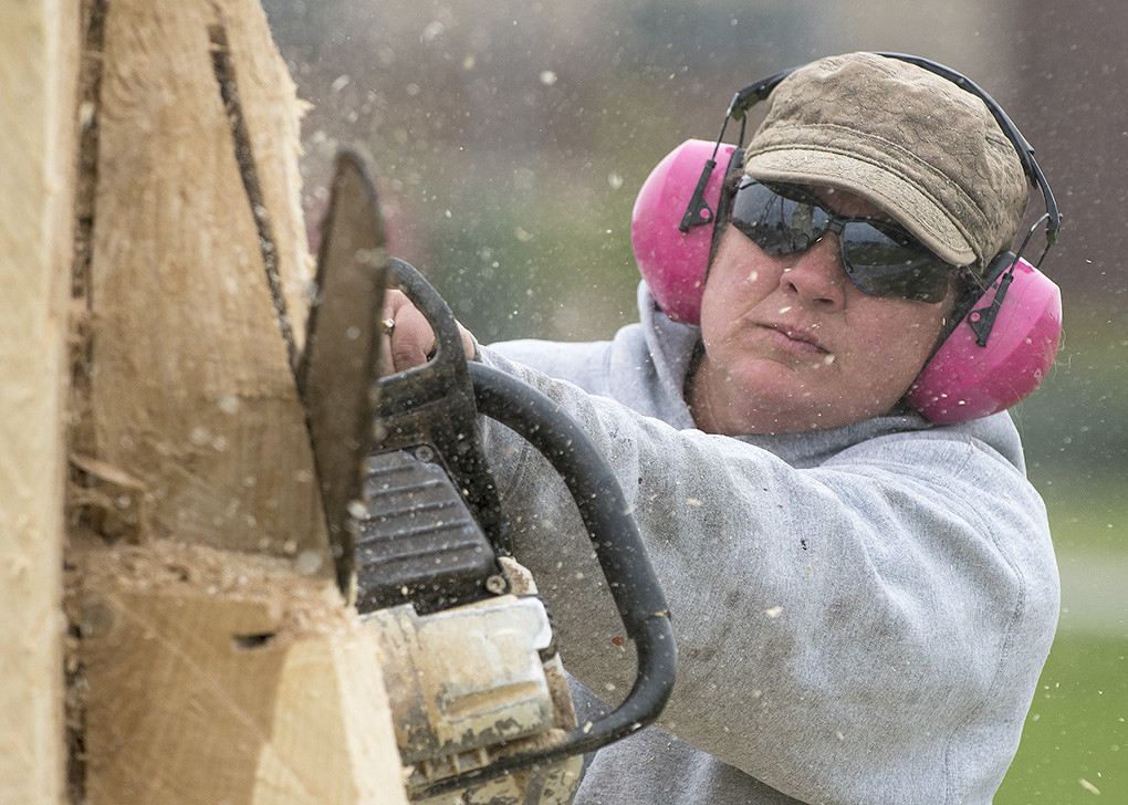 Wood chips fly as Christy Muecke (a.k.a. the 'Chick with the Chainsaw') works on a sculpture near the main entrance to the Park County School District No. 1 Support Services Building. The sculpture was made possible after several dying trees had to be removed in front of the building earlier this year.