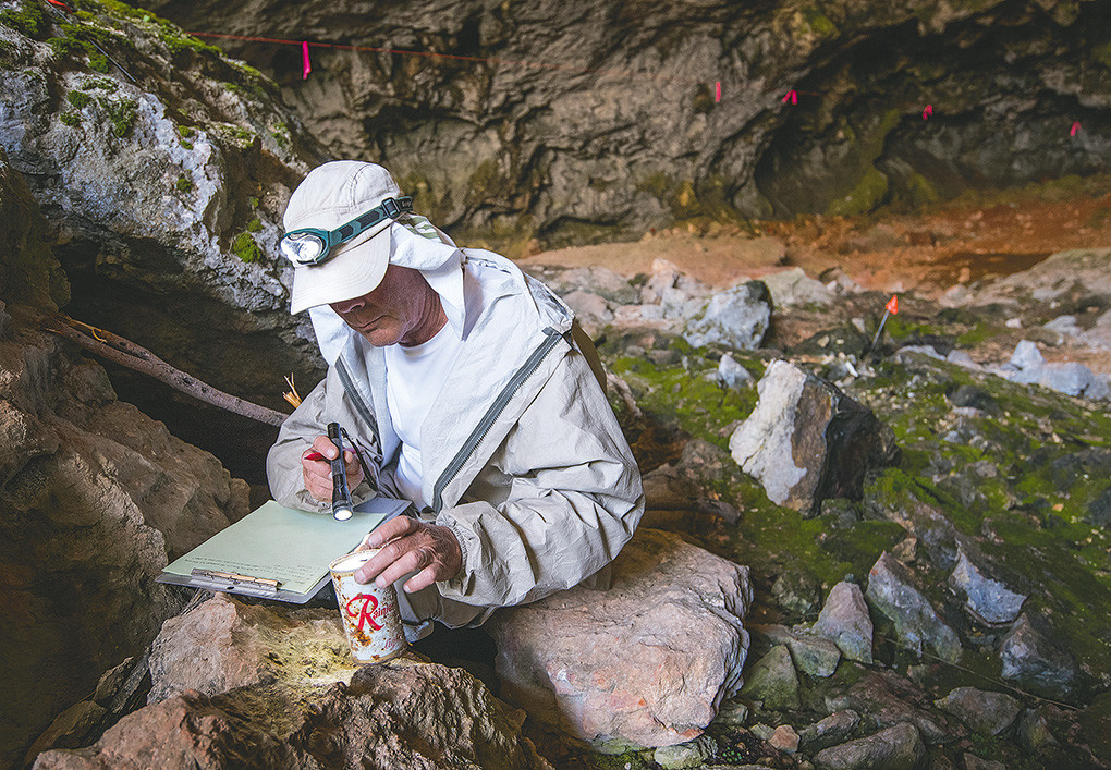 Russell Richard, an archaeologist from Cheyenne, checks a Rainier beer can, left in the cave in the early 1960s. Richard found several cans in the cave, dating from 1908 to 1968.