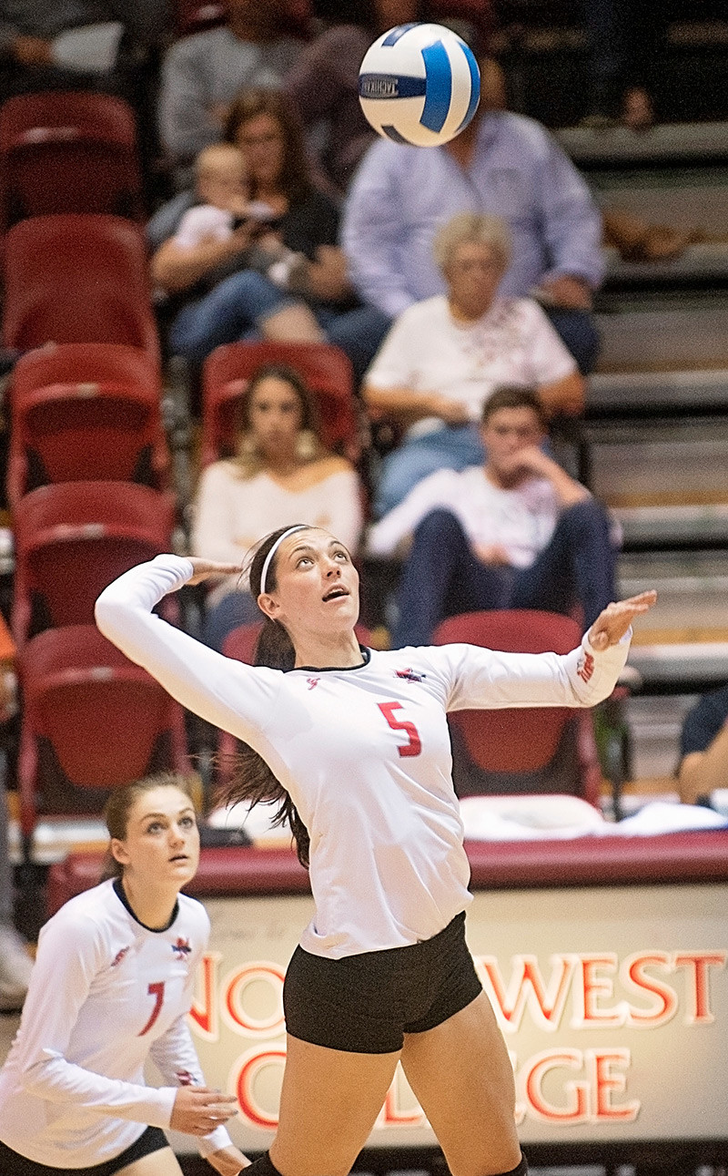 Lady Trapper outside hitter Shania Warren winds up for a kill Saturday against Western Wyoming as teammate Caitlyn Costa looks on. NWC won the match 3-1.