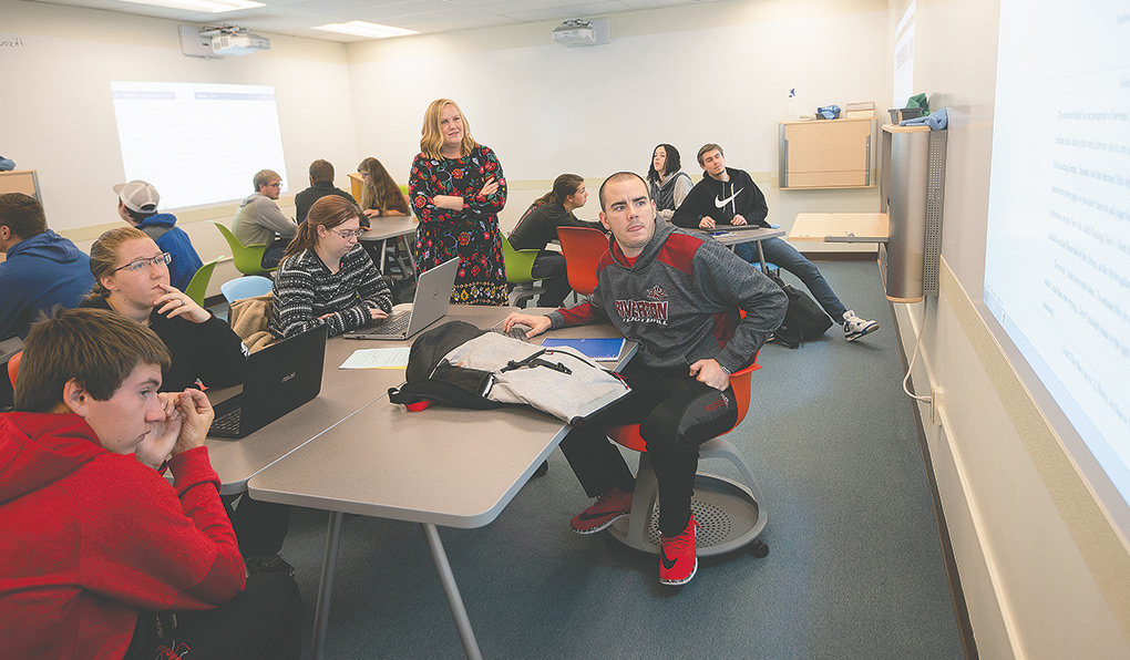 Northwest College instructor Heidi Hansen works with students in her general studies first year seminar class Wednesday morning on the NWC campus. The college is striving to reverse a trend that has seen enrollment decline in eight of the last nine years.