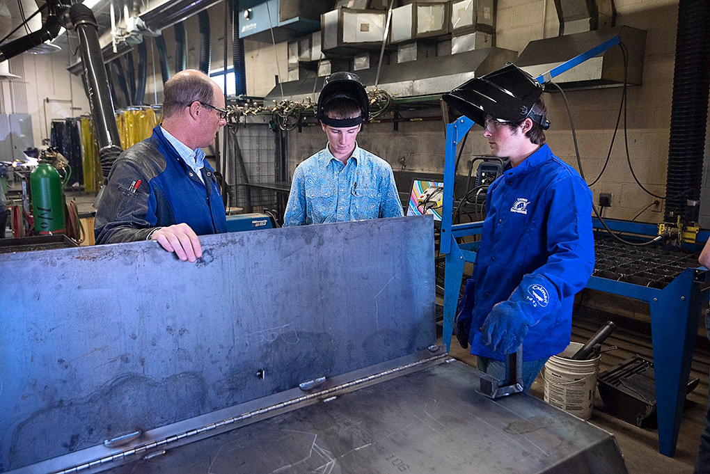 PHS ag and welding instructor Bryce Meyer visits with students Corey Linebaugh and Ryley Meyer during class earlier this month.